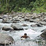 Los jovenes juegan con troncos de balsamo como si fueran flotadores desplazandose por el rio Escui. Comunidad indigena Yorquin de habla Bri-Bri. Costa Caribe. Costa Rica