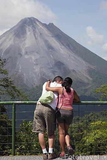 Pareja frente al volcan Arenal desde lo alto del mirador de la empresa Sky Adventures. La Fortuna. Costa Rica