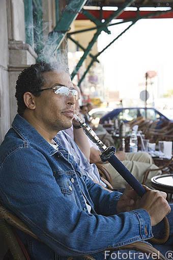 Chico fumando un narguile en un cafe de la calle 26 de Julio. Ciudad de ALEJANDRIA. Egipto