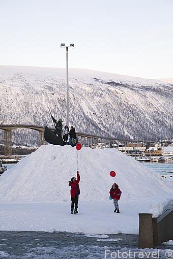 Monumento a los cazadores de ballenas en Stortorvet y jovenes divirtiendose. Ciudad de Tromso. Noruega