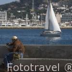 Velero y hombre leyendo junto al puerto. Barrio de Sa Penya. Ciudad de IBIZA. Islas Baleares. Mar Mediterraneo. España