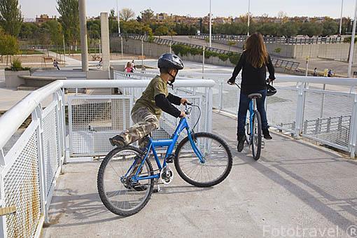En bicicleta atravesando un puente sobre el canal. Parque Juan Carlos I. Campo de las Naciones. Madrid. España