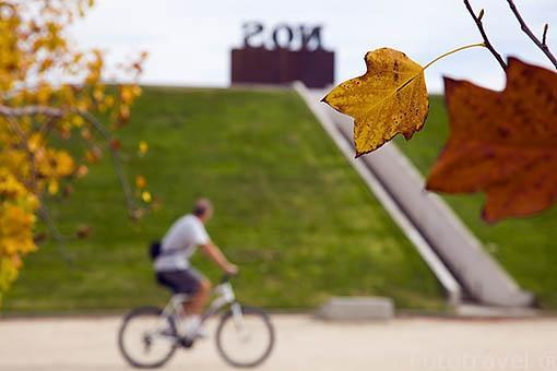 """Ciclista y detras la escultura """"Los Cantos de la Encruicijada"""" por Leopoldo Maler. Parque Juan Carlos I. Campo de las Naciones. Madrid. España"""