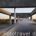 """Uno de los varios puentes que atraviesa el canal y aspersores de agua. Al fondo izquierda la obra """"Espacio Mexico"""". Parque Juan Carlos I. Campo de las Naciones. Madrid. España"""