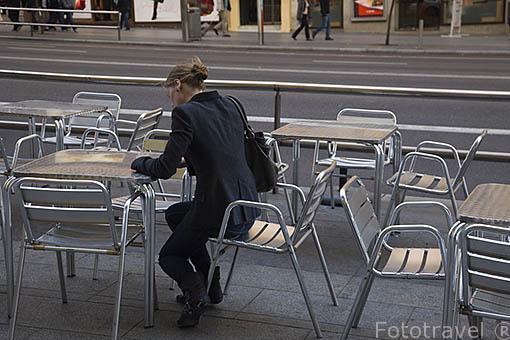 Chica sentada en una terraza en la Gran Via. Madrid. Comunidad de Madrid. España