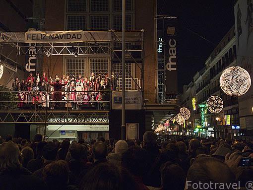 Calle Preciados decorada para Navidad. Niños cantando villancicos en la plaza de Callao, junto a la Gran Via. Madrid. España