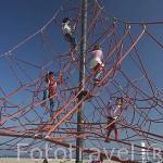 La playa de Pinedo y chicos jugando subidos en una araña gigante. VALENCIA. España