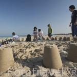 Padre con hijo y amigos construyendo castillos de arena. Playa de Pinedo. VALENCIA. España