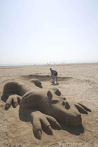 Artista ambulante trabajando con arena para crear una efimera obra con forma de dragon en la playa de El Cabañal. VALENCIA. España