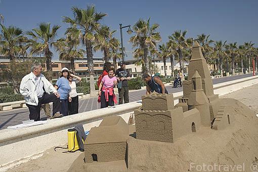 Artista ambulante trabajando con arena para crear una efimera obra con forma de castillo en la playa de El Cabañal. VALENCIA. España