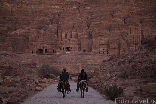 Beduinos en sus asnos, detrás la pared con las tumbas reales. Ruinas de PETRA. Patrimonio de la Humanidad, UNESCO. Jordania