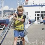 Un joven llevando un mastil y vela para su embarcación. Escuela de vela. Puerto deportico y club nautico de la ciudad de VIGO. Galicia. España