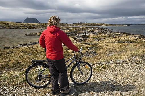 Ciclista paseando por la isla de VEGA. Al fondo la montaña de la isla de Sola. Patrimonio de la Unesco. Noruega