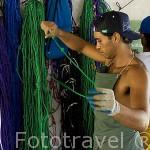 Trabajadores seleccionando el color de su cordel para las ristras de ostras y anotando cantidades. Granja de Gauguin´s Pearl. Atolon RANGIROA. Archipielago de Tuamotu. Polinesia Francesa.