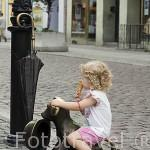 """Niña sentada sobre la escultura de """"Piesek Filutek"""" en una esquina de la plaza del Ayuntamiento. Centro historico de la ciudad de TORUN. Kuyavia- Pomerania. Polonia"""
