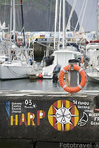 Embarcaciones y al fondo pinturas realizadas por marineros en el suelo del puerto deportivo de Horta. Isla de FAIAL. Azores. Portugal