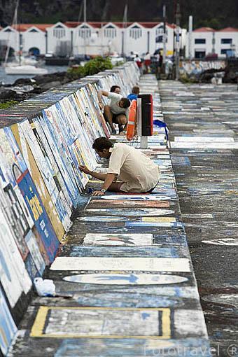 Muro y un marinero pintando. Puerto deportivo de Horta. Isla de FAIAL. Azores. Portugal