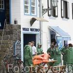 Turistas poniendose el chaleco salvavidas junto al museo de los balleneros. En Lajes do Pico. Isla de PICO. Azores. Portugal