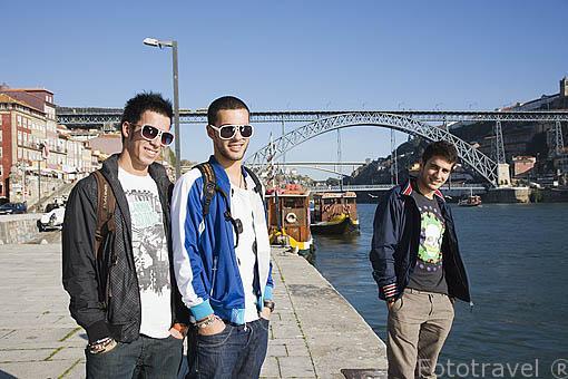 Chicos junto al rio Duero. Al fondo el puente de Luis I. Ciudad de OPORTO. Portugal