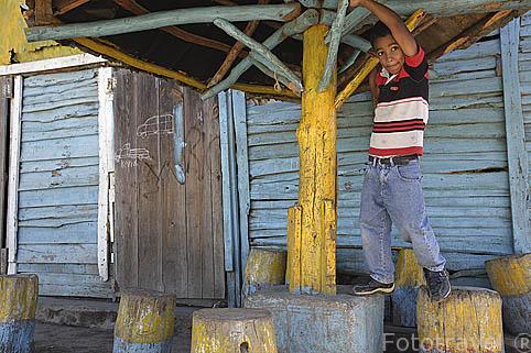 """Guilson jugando junto a un colorido """"bohio"""". Pueblo de CONSTANZA. Caribe. Isla Republica Dominicana"""