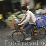 Chico en bicicleta. Mercado Pak Kkhlong Talad. Ciudad de BANGKOK. Tailandia