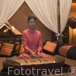 Chica tocando un Khim, instrumento musical de percusion de origen chino. Triangulo de Oro. Chiang Rai. Tailandia