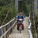 Motorista atravesando un puente de madera. Donacion del gobierno japones al pais. Poblado de KEAW VUA DAM. junto al rio Kok. Chiang Rai. Tailandia