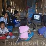 Interior de una vivienda y familia de la tribu Lahu rojo viendo la TV, electricidad que llega gracias a placas solares donadas por el gobierno. Poblado de CHA KUE. Chiang Rai. Tailandia