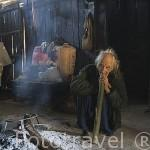 Interior de una vivienda y anciano fumando tabaco. Poblado de los chinos Hmong blanco. En HMONG CHANG KIEN. Chiang Mai. Tailandia