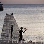 Puesta de sol sobre un pequeño embarcadero y chicos jugando. Isla de KO LANTA YAI. Mar de Andaman. Tailandia