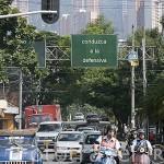 """Calle y cartel indicativo curioso """"Conduzca a la defensiva"""" y dispuesto al sentido contrario de la circulación. MEDELLIN. Departamento de Antioquia. Colombia"""