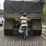 Chico en bicicleta remolcado por un camion en una subida. MEDELLIN. Departamento de Antioquia. Colombia