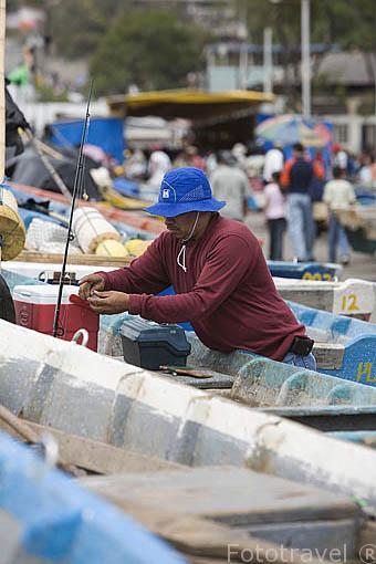 Pescador preparando sedal en el muelle del puerto de La Libertad. Departamento de la Libertad. El Salvador. Centro américa.
