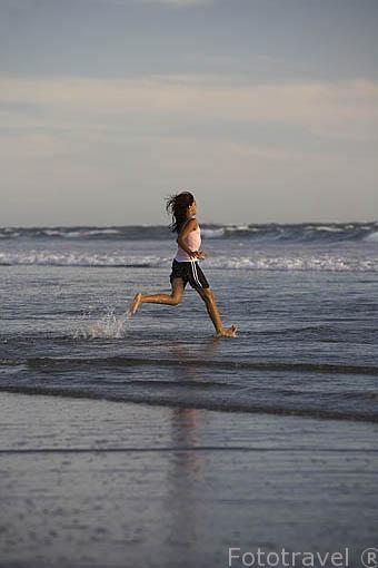 Chica corriendo. Playa al sur de La Libertad. El Salvador. Centro américa.