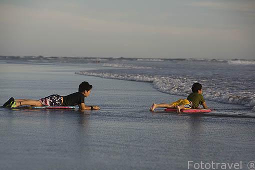 Chicos con sus tablas de bodyboard. Playa al sur de La Libertad. El Salvador. Centro américa.