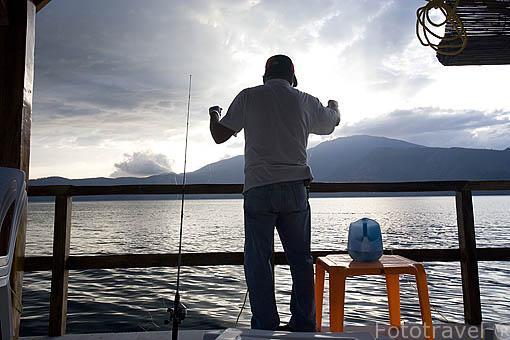 Pescador desde el muelle. Lago de Coatepeque. El Salvador. Centro américa.