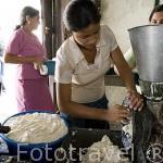 Mujeres triturando alimentos en el unico molino situado junto a la iglesia. Pueblo de SUCHITOTO. El Salvador. Centro américa.