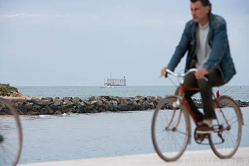 Ciclistas y el fuerte Boyard frente a las costas de la isla de Oleron. Francia