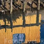 Reflejo de una escalera y colorida casa de madera en el agua de un canal en marea baja. Puerto ostricola de LE CHATEAU D´OLERON. Isla de Oleron. Francia