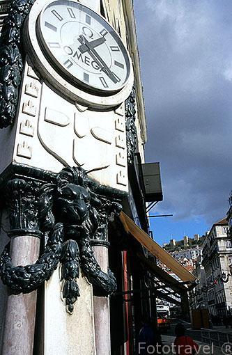 Un reloj en la esquina de la calle R. Betesga. Zona del Rossio. Detras el castillo de San Jorge. LISBOA. Portugal