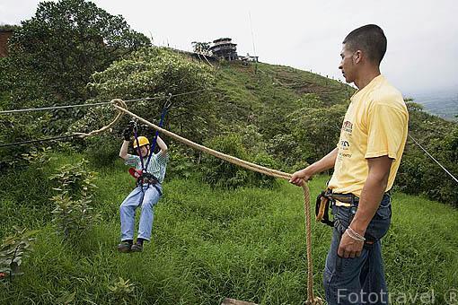Practicando tirolina en el complejo turistico Territorio Paraiso, al fondo el mirador Maloca de los Vientos. Valle del Cauca. COLOMBIA.