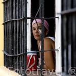 Chica en una ventana enrejada. Calle Real del Medio.Ciudad colonial de MOMPOX. Patrimonio de la Humanidad, UNESCO. Isla más grande de Suramerica. Colombia. Suramerica