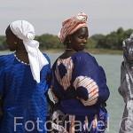 """Mujeres vestidas con sus """"boubous"""" observando el barco Bou EL Mogdad en el muelle de PODOR. Al norte de Senegal"""