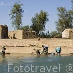 Gente lavando enseres en la orillas del rio Senegal. Detras sus casas de adobe. SENEGAL