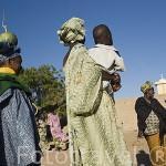 Mujeres vestidas con sus boubous. Al fondo la mezquita del pueblo de FANAYE WALO. Situado junto al rio Senegal. Norte de Senegal