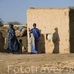 Mujeres vestidas con sus boubous junto a sus casas de adobe en el pueblo de DEGUEMBERE. Rio Senegal. Norte de Senegal